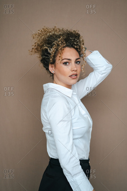 Young female with curly hair and in formal apparel posing in studio and looking at camera