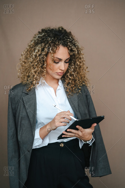 Focused female entrepreneur in formal outfit using tablet with stylus and rejoicing over project accomplishment on brown background in studio