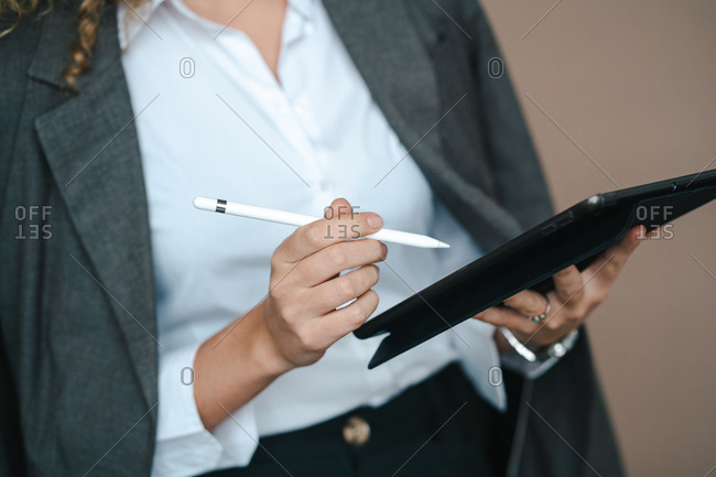Close up of anonymous female entrepreneur in formal outfit using tablet with stylus and rejoicing over project accomplishment on brown background in studio