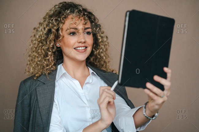 Cheerful female entrepreneur in formal outfit using tablet with stylus and rejoicing over project accomplishment on brown background in studio