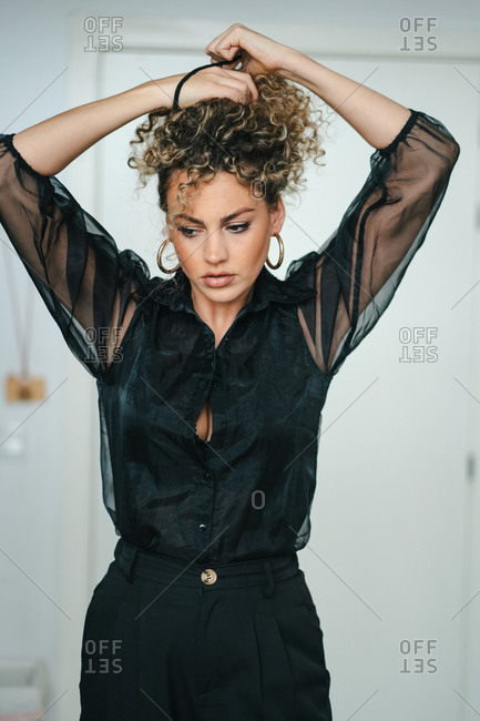 Serious female with curly hair and in elegant black clothes standing in room and making ponytail while looking away
