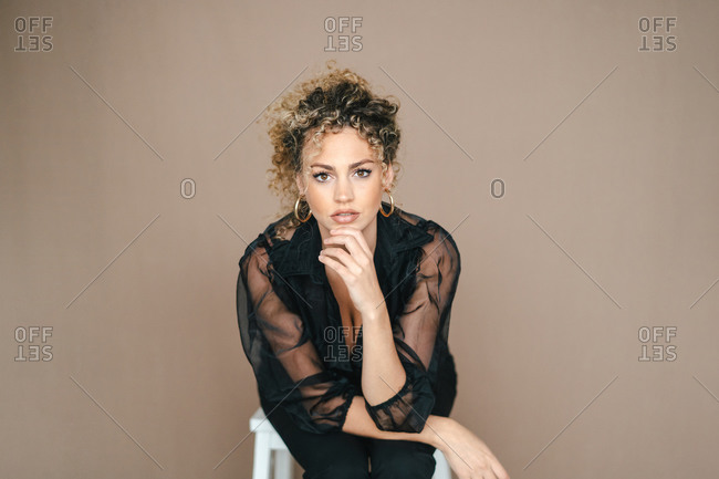 Pensive female in elegant black outfit leaning on hand and looking at camera on brown background