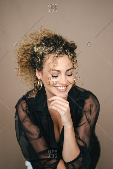 Cheerful female in elegant black outfit leaning on hand and looking down with closed eyes on brown background