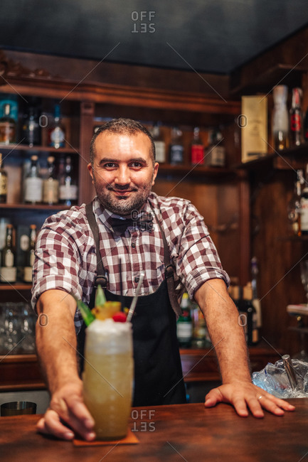 Happy male mixologist putting glass of cold exotic cocktail with fruits and ice on counter during work in bar looking at camera
