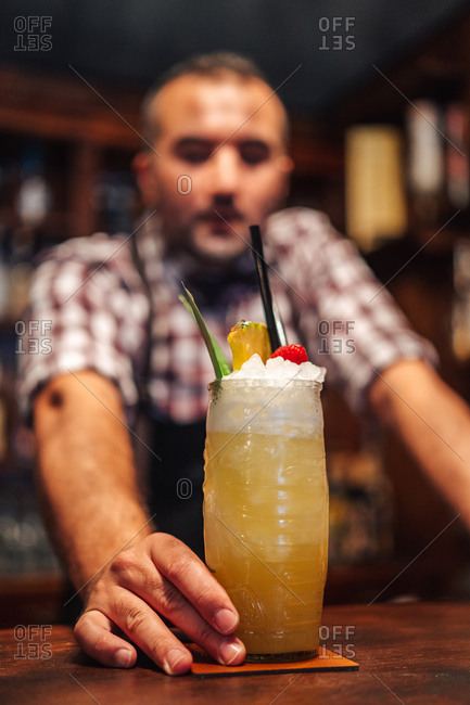Soft focus of male mixologist putting glass of cold exotic cocktail with fruits and ice on counter during work in bar looking at camera