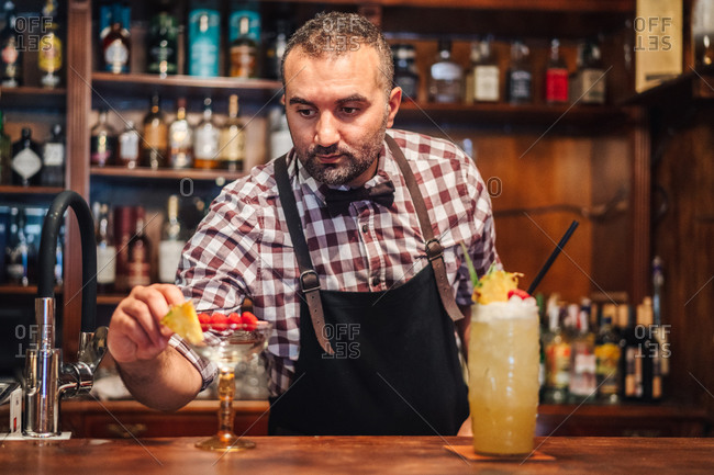 Middle aged man in apron and checkered shirt decorating glasses of cocktails with pieces of pineapple and raspberries on counter in pub