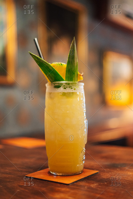 Glass cup of tropical cocktail with pineapple and leaves placed on counter in bar