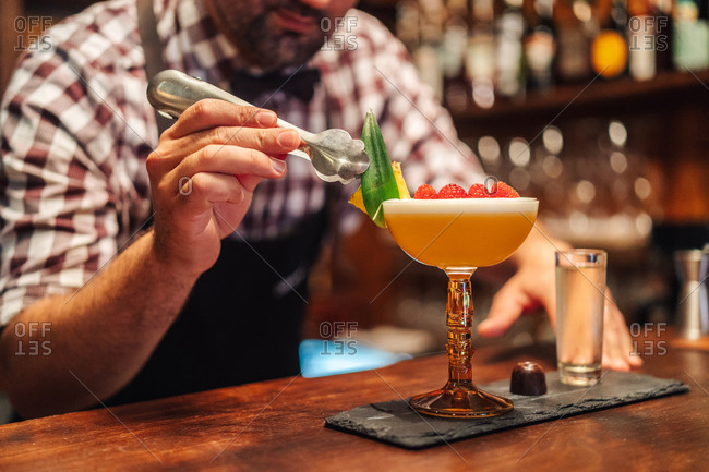 Unrecognizable barkeeper putting leaf on tropical cocktail with raspberries and pineapple near chocolate candy and liquor in pub