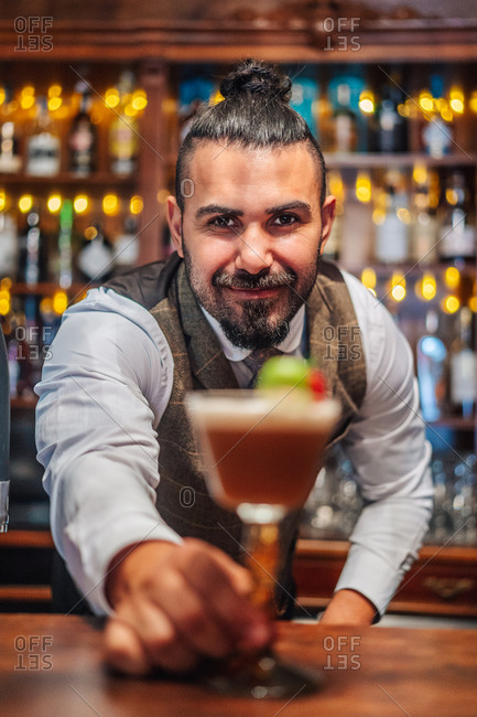 Happy bearded male mixologist putting glass of cold exotic cocktail with fruits and ice on counter during work in bar looking at camera