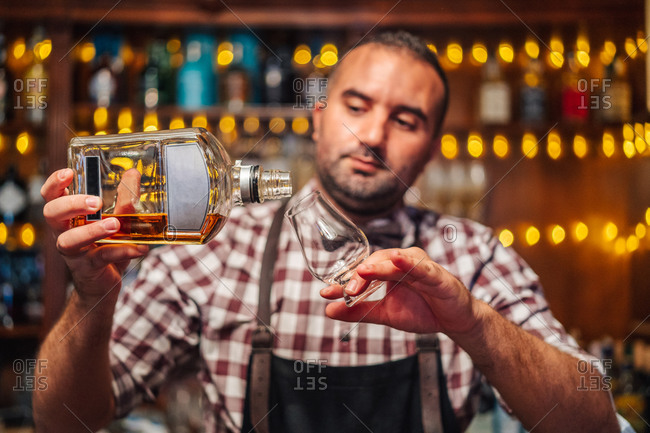 Crop brutal male bartender in apron pouring brandy in glass on counter