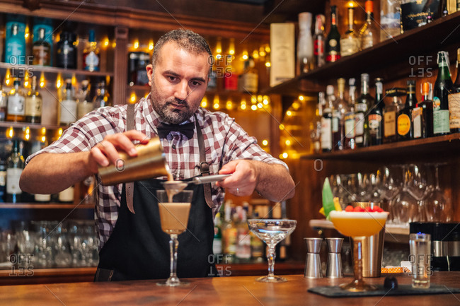 Bearded barkeeper adding ingredient from shaker into glass goblet while preparing cocktail in pub