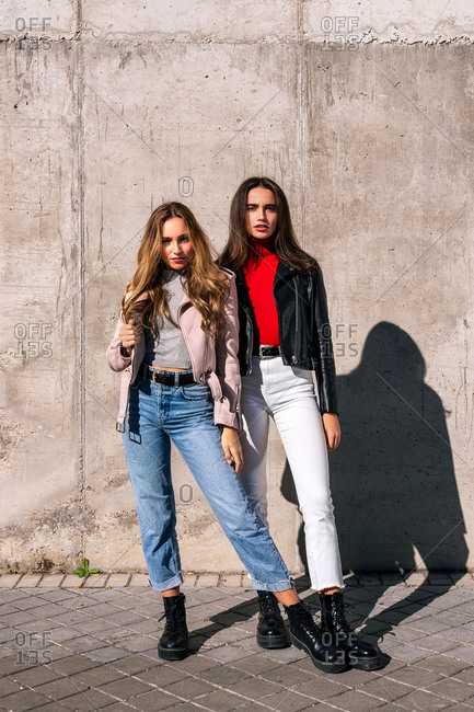 Female millennials in trendy boots and jackets standing on urban street on sunny day