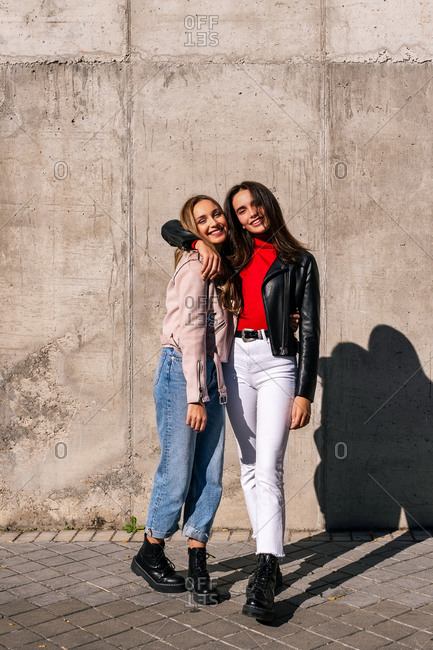 Young female friends in stylish outfits hugging and looking at camera while standing in city and enjoying stroll together