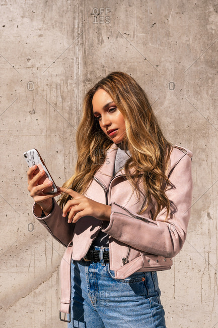 Serene female millennial standing on street and messaging on social media with friends via smartphone