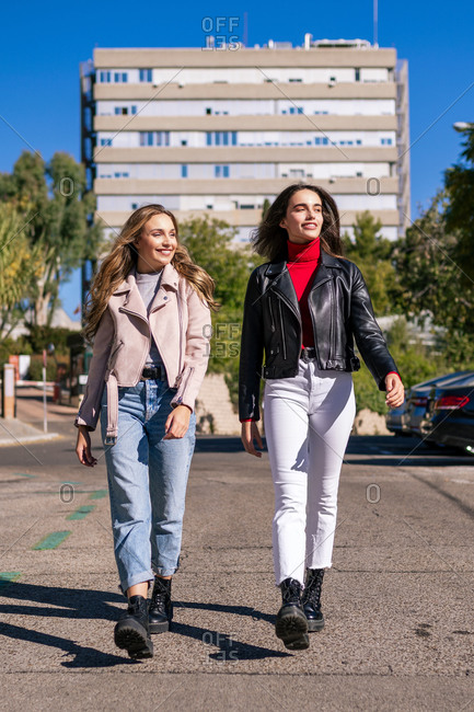 Delighted female friends in stylish wear walking along city street while looking away and spending time together