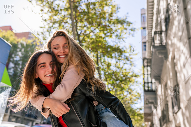 Positive woman piggybacking best friend while having fun on street and spending weekend together