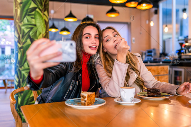 Satisfied female best friends sitting at table in cafeteria and taking selfie on smartphone while hugging and enjoying time together