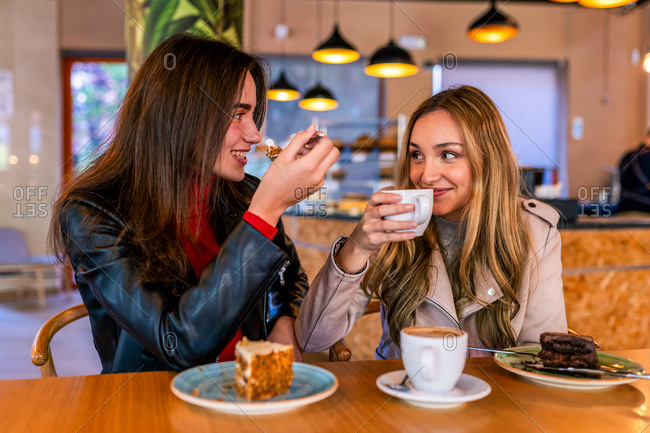 Cheerful females sitting at table in cafe and looking at each other while drinking coffee and eating delicious desserts