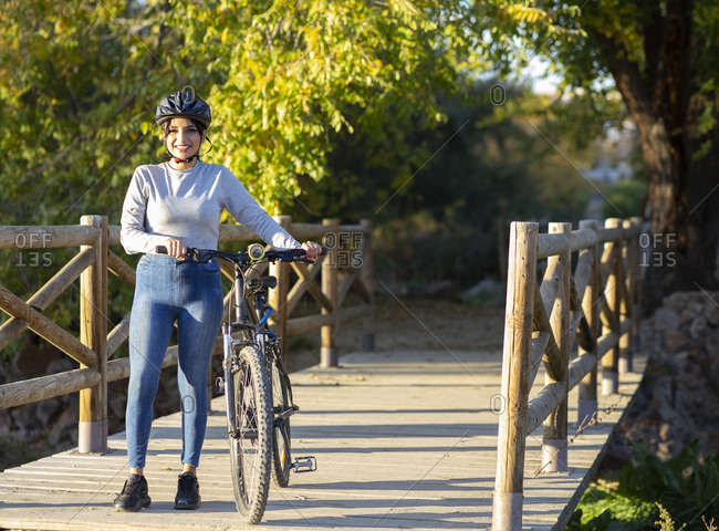 Full length of smiling young active female in protective helmet standing with bicycle on wooden bridge near trees in sunny autumn day in countryside