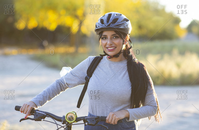 Full body of positive young female in activewear and helmet riding bicycle through autumn forest with golden foliage in sunny day in countryside