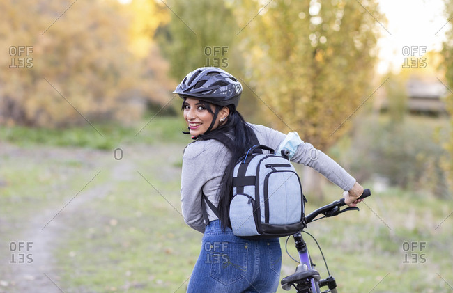 Back view of happy young female bicyclist in protective helmet with backpack looking over shoulder at camera while standing with bicycle on trail in autumn forest