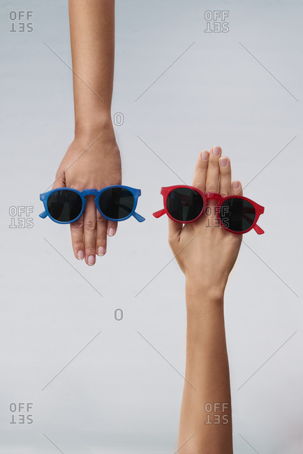 Top view of crop hands of anonymous women demonstrating stylish sunglasses with black lens and red and blue plastic frames against gray background