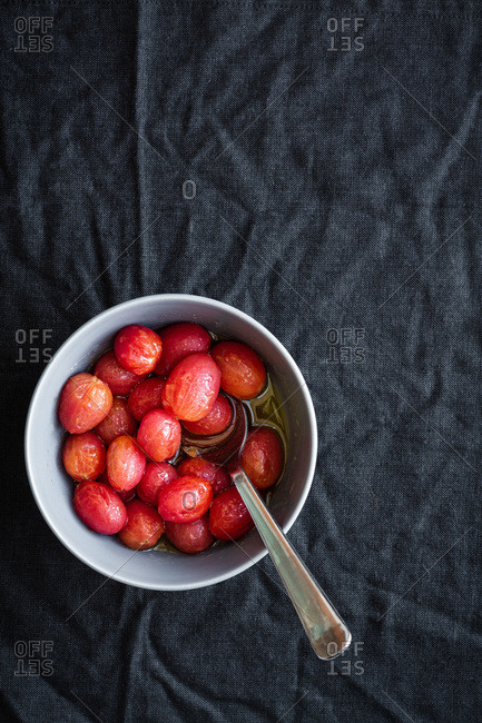 Top view of bowl full of marinated red grape tomatoes with spoon placed on black surface