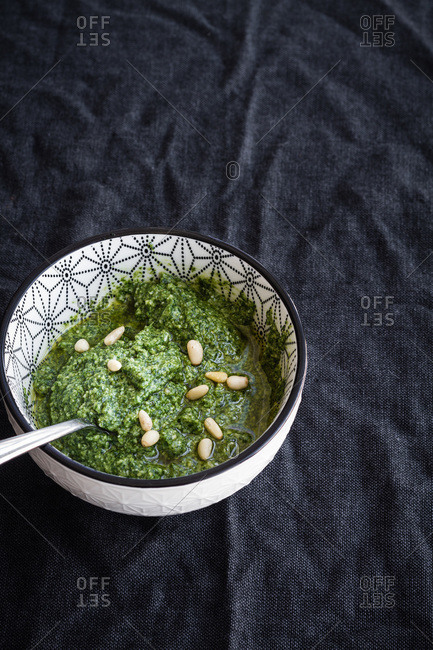 From above of ceramic bowl with fresh aromatic green pesto sauce with pine nuts placed on black cloth