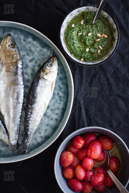 From above composition with plate with salty herring fish placed near bowls with pesto sauce and marinated tomatoes on table