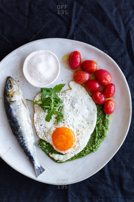 From above fried egg served with salty fish and marinated tomatoes and garnished with pesto sauce