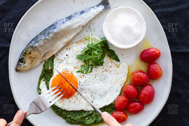 From above crop anonymous person eating fried egg served with salty fish and marinated tomatoes and garnished with pesto sauce