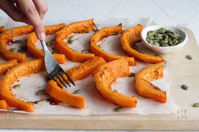 Unrecognizable crop cook with fork smashing baked pumpkin slices with fork placed on wooden cutting board in kitchen