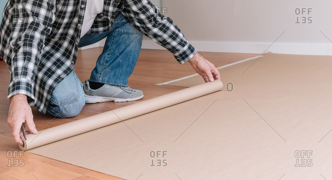 Crop unrecognizable male painter covering floor with craft paper while preparing room for painting and renovation