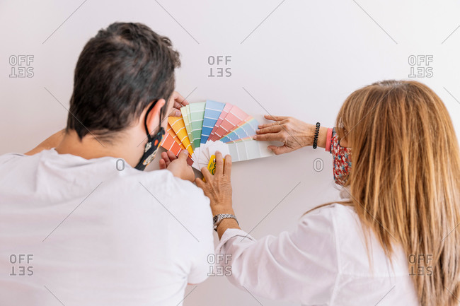 Back view of male worker and woman with paper palette picking color for walls during renovation process in apartment