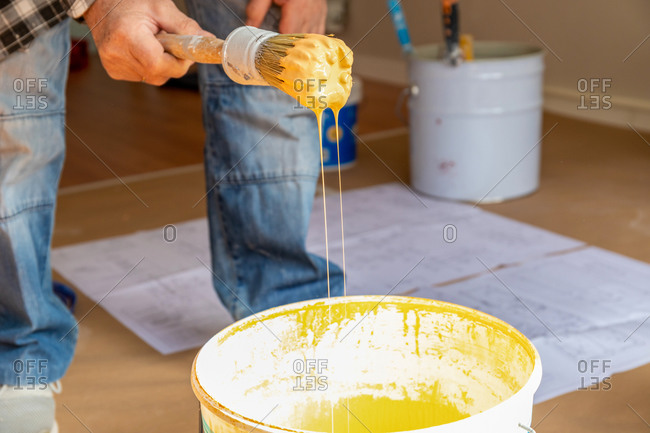 Crop anonymous male worker standing near bucket with brush in yellow paint while working and renovating apartment