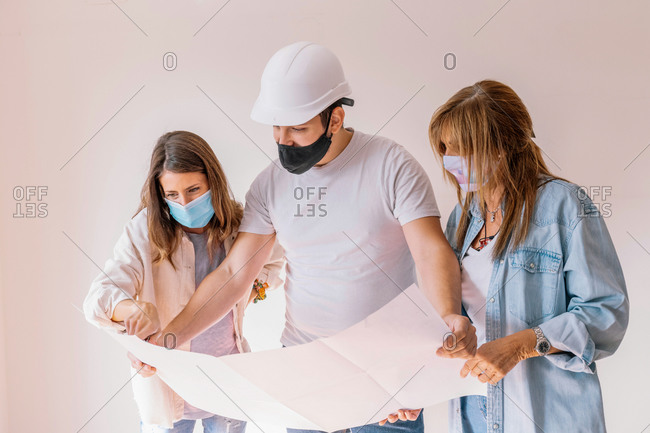 Women in masks and male builder in hardhat examining project of flat renovation