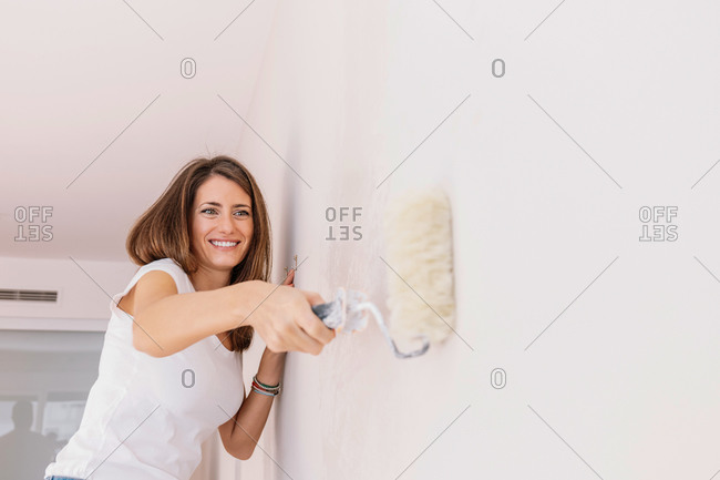 Side view of cheerful female with paint roller coloring wall while renovating apartment