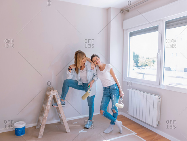 Young female with roller leaning on mature mother and gesturing thumb up while painting wall during renovation at home