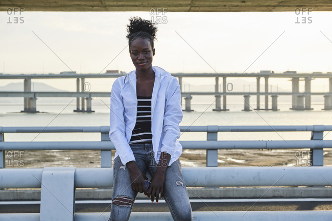 Serious young African American female in casual outfit sitting on railing near sea on urban embankment and looking at camera