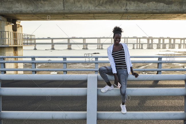 Full body of optimistic young African American female in casual outfit sitting on railing near sea on urban embankment and looking at camera
