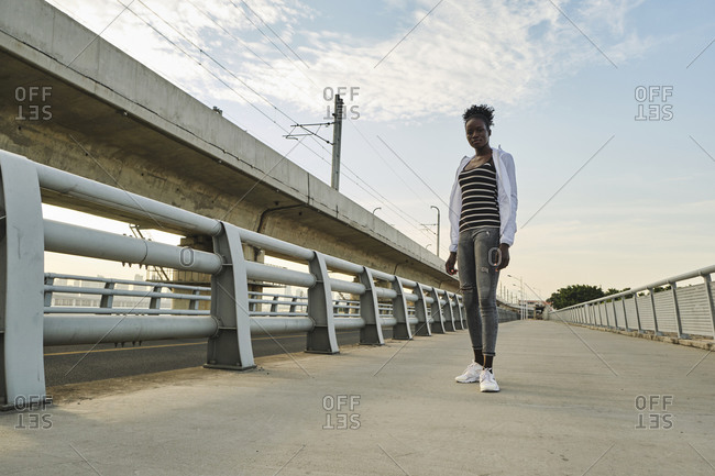 Full body of confident young black female student with Afro hairstyle wearing casual clothes looking at camera while standing near fence on urban embankment and enjoying summer day