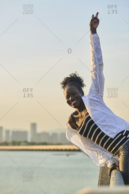 Side view of happy laughing young African American female in casual wear leaning over fence while enjoying free time on urban seafront