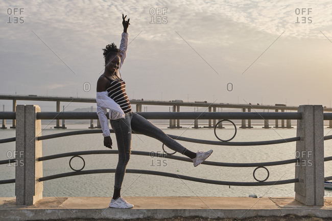 Full body side view of playful carefree young African American female student in casual clothes standing on one leg with arm raised near railing against urban seafront