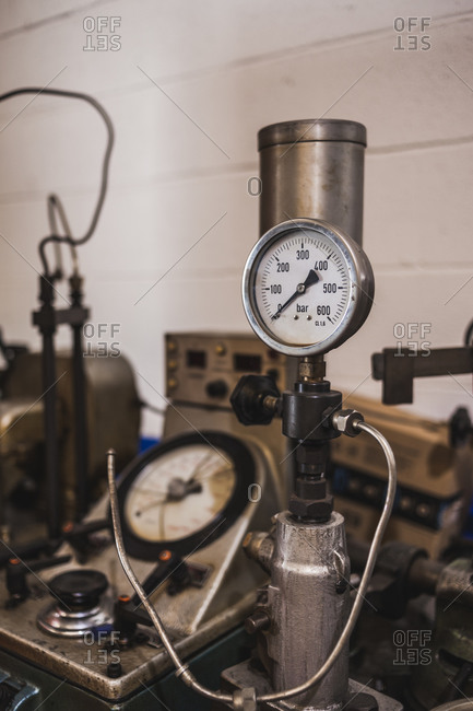 Shabby metal pressure gauge for tires placed near rusty professional machine in garage