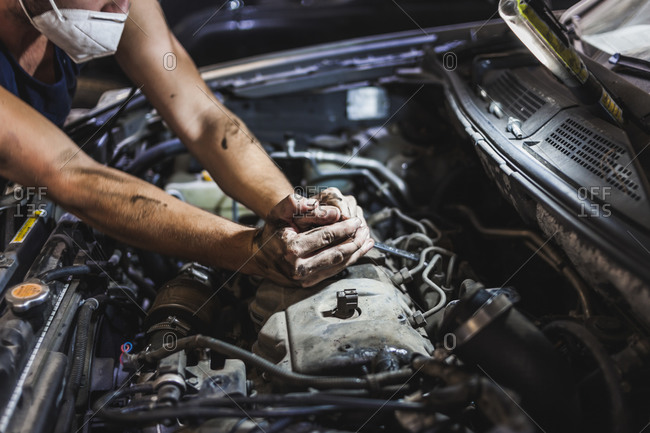 Unrecognizable male technician putting cables into motor while fixing vehicle during work in garage