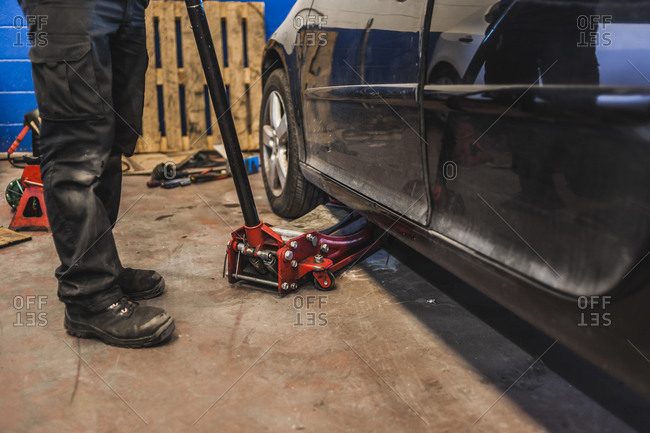 Unrecognizable technician lifting modern vehicle with hydraulic jack during work in professional garage