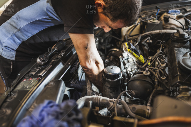 Side view of adult male mechanic illuminating engine with flashlight and checking motor of vehicle during work in garage