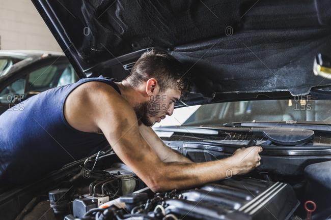 Side view of dirty man loosening screws on motor while fixing car in garage