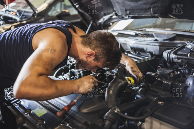Male mechanic illuminating engine with flashlight and checking motor of vehicle during work in garage
