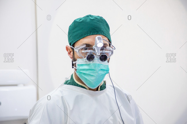 Male doctor in medical mask and bilocular glasses standing in modern dental clinic and looking at camera